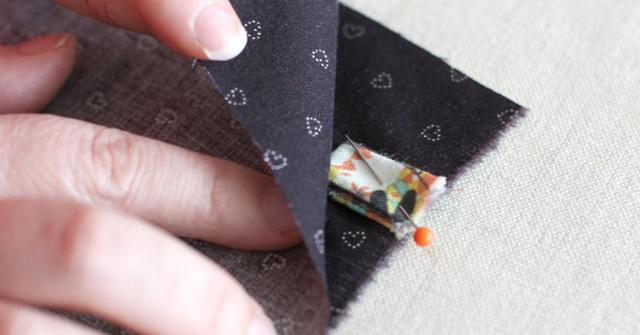 | Le ruban est plié et glissé entre les deux pans de tissus extérieur.